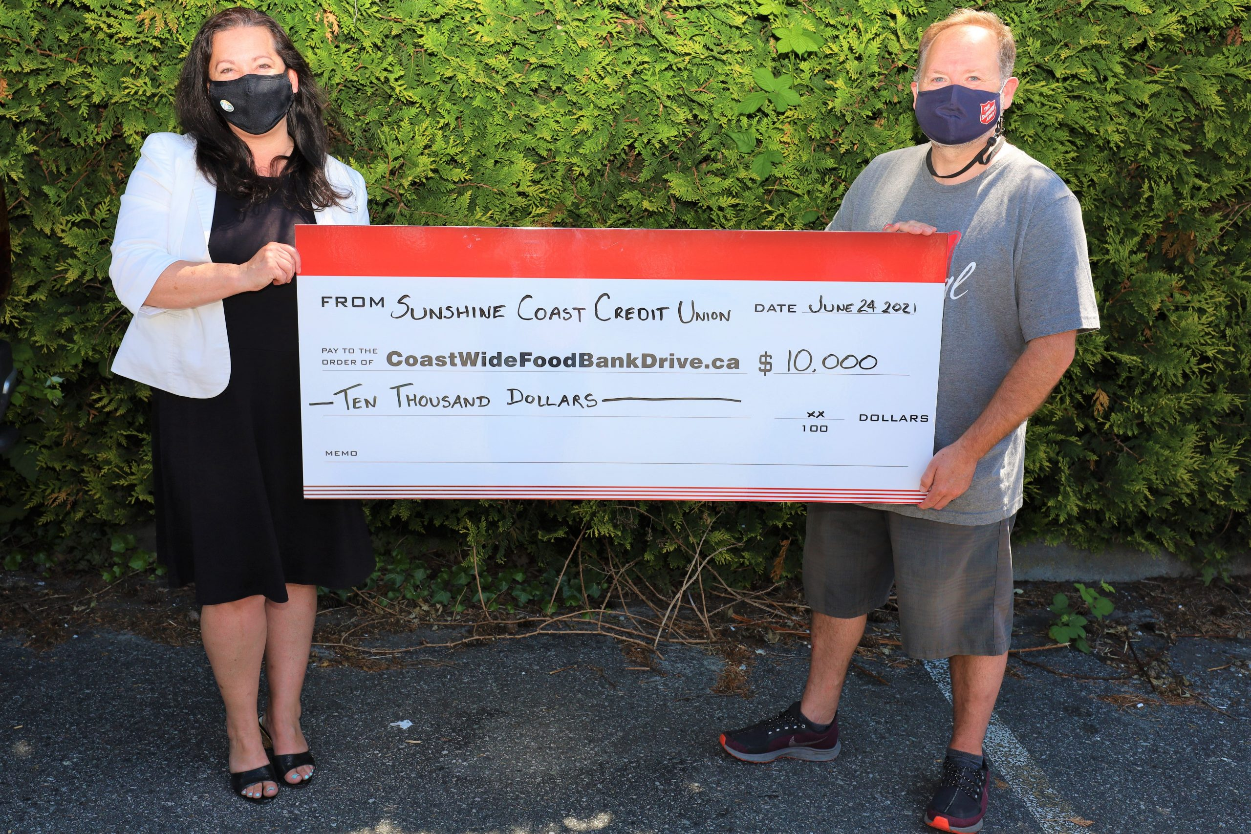 Employees of the Sunshine Coast Credit Union stand with a large cheque
