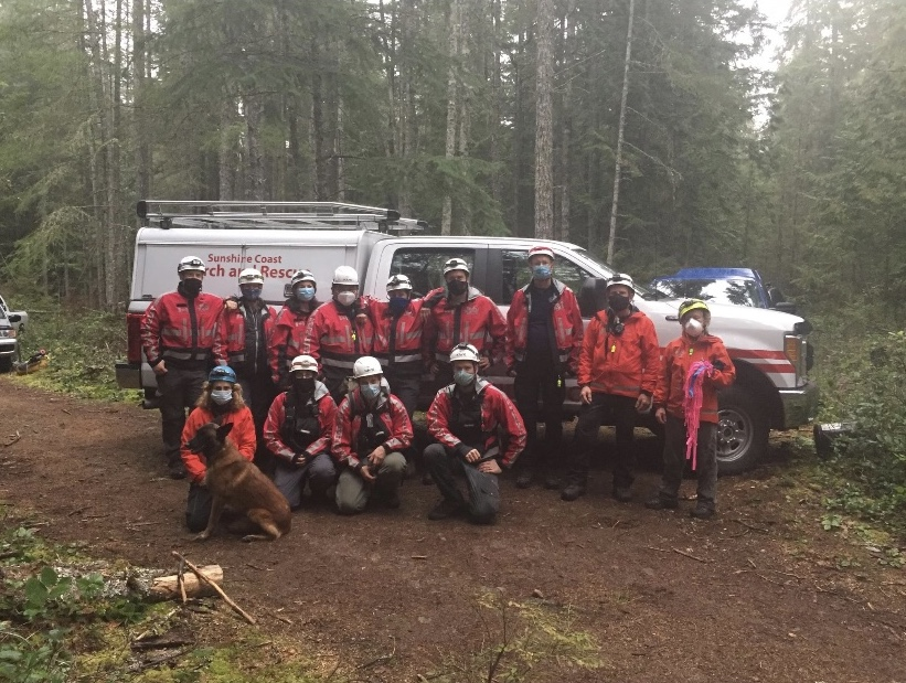 The Sunshine Coast Search and Rescue Association stands in a group in the forest.